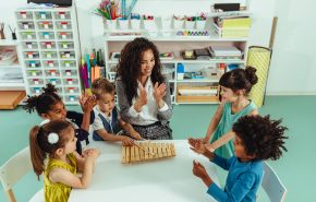 Teacher helping cheerful children playing some musical toys at kindergarten