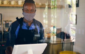 worker in mask stands behind a glass partition at a register